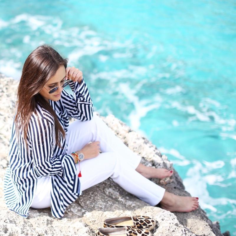 Bild auf Klippen, gestreifte Bluse, weiße Hose, Sonnenbrille