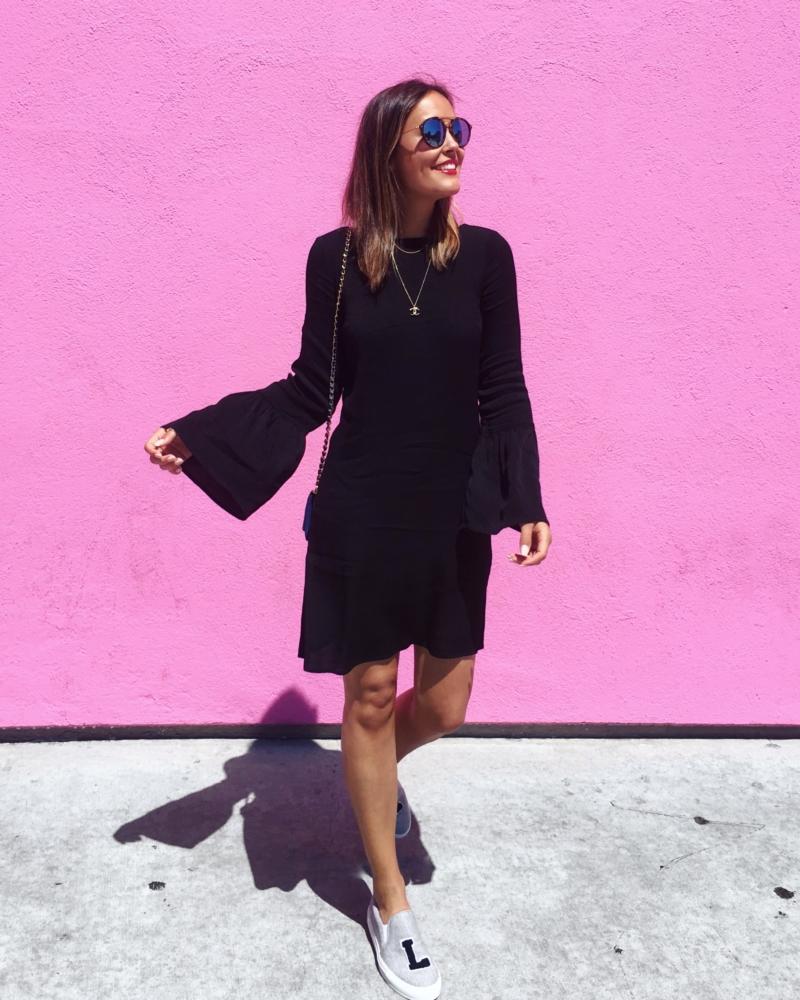 pinke Wand, schwarzes Kleid
